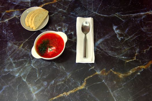 Traditional Russian soup Borsch , white bread and a spoon on a napkin. Close-up.
