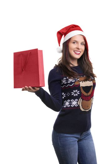 A portrait of a beautiful smiling young girl in winter clothes wearing Santa's hat, holding a shopping a bag, isolated on white background.