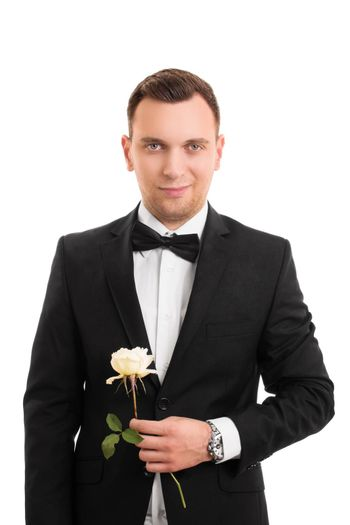 A portrait of a smiling handsome young man in a suit holding a flower, isolated on white background.