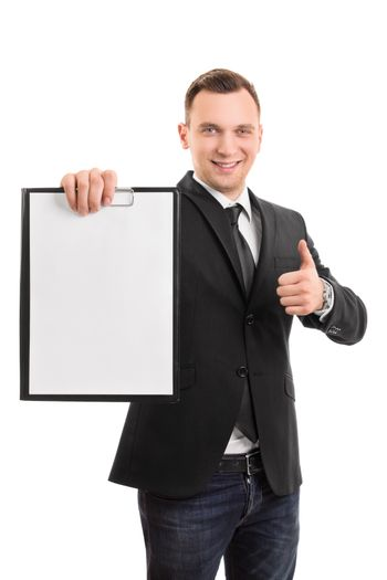 A portrait of a young smiling businessman holding a blank clipboard and showing a thumb up gesture, isolated on white background.