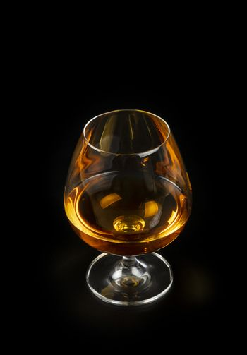 Glass of cognac or brandy isolated on black