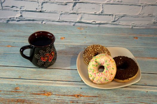 Plate with several multi-colored donuts in the glaze and a dark ceramic cup with tea. Close-up.