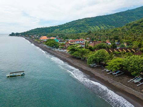Aerial view of Amed beach in Bali, Indonesia. Traditional fishing boats called jukung on the black sand beach and one on the sea.