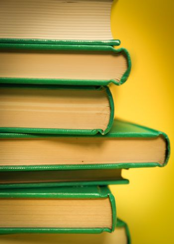 crop of a vertical stack of books. Yellow background and green books.