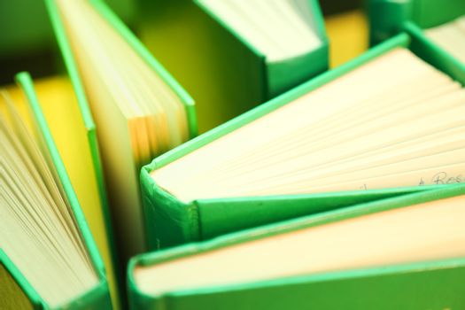 Green books on a yellow background - open pages