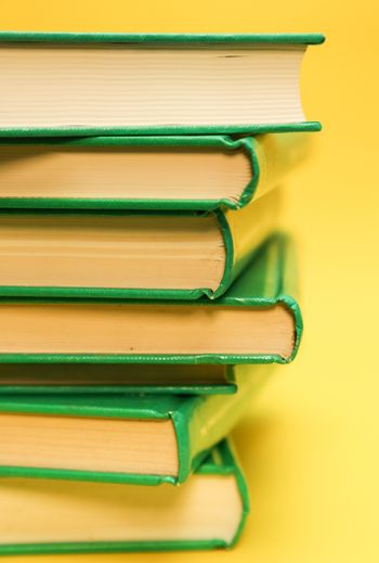 Book pile, over a yellow background - Education books background