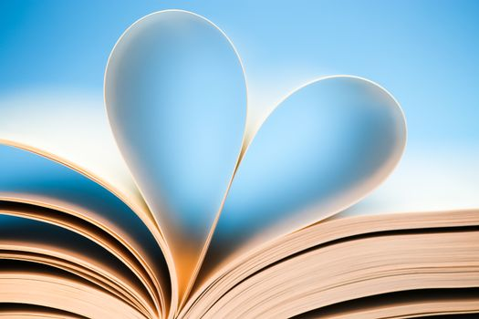 Book pages on blue background, glowing heart formed by book