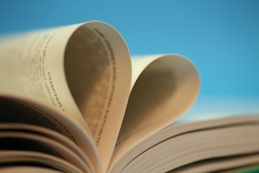 Heart shape book pages, over blue background