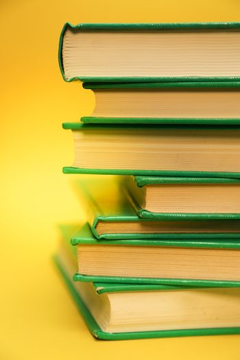 Yellow background and a pile of books, studying text books.