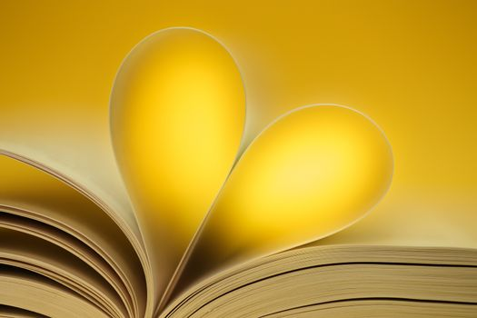 Yellow heart, glowing love of reading. Book forming a heart.