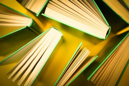 Books over a yellow background. Education books stacked and shot top down