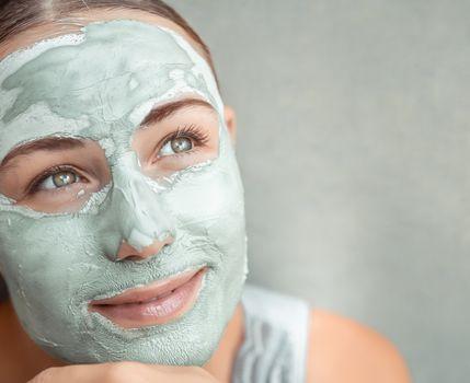 Beautiful girl doing facial mask