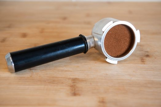 portafilter with temping ground coffee on wooden table.