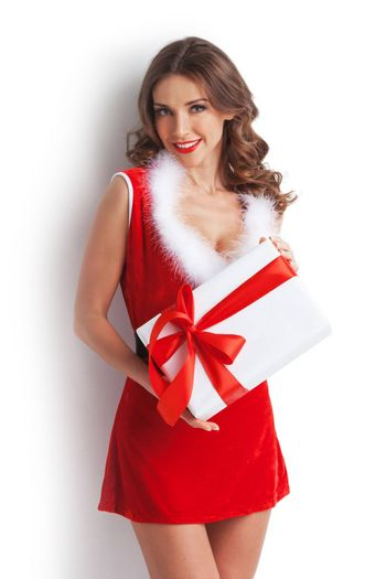 Smiling cute girl in red christmas outfit holding gift box on white background