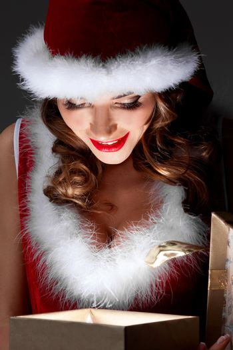 Beautiful santa girl opening glowing gift and smiling
