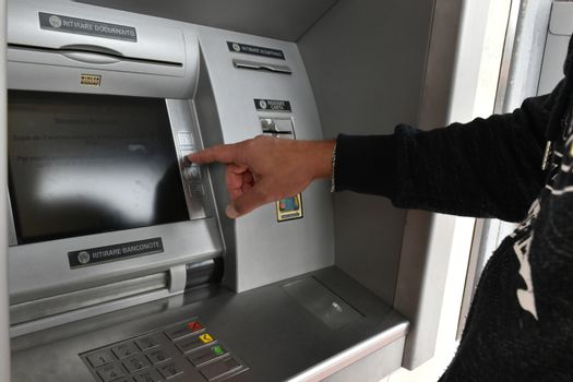 Man while taking money at the bank cash machine atm
