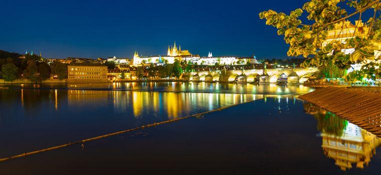 Prague by night. Prague Castle and Charles Bridge reflected in Vltava River. View from Smetana Embankment. Praha, Czech Republic