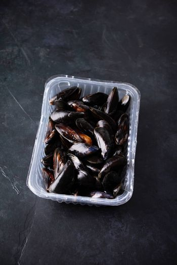 Fresh uncooked raw big mussels on dark background