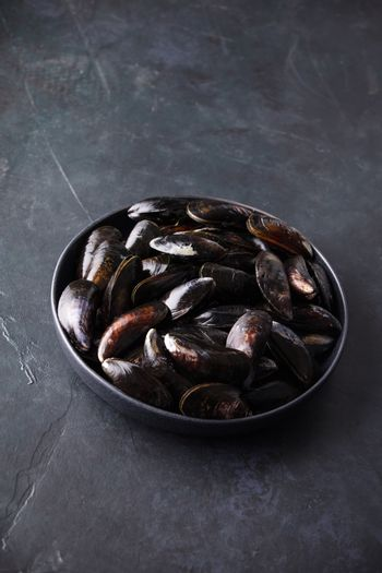 Bowl with fresh raw mussels ready to cook on dark background