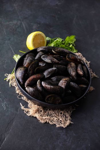 Bowl with fresh raw mussels with lemon and parsley ready to cook on dark background