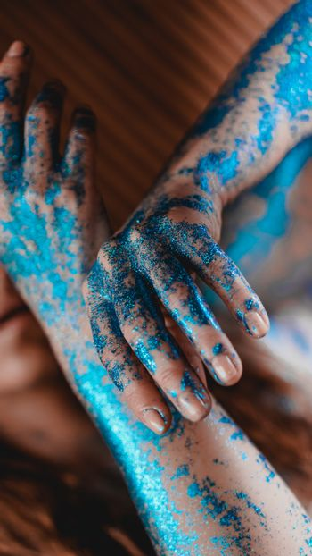 Blue glitter on woman hands. Smooth movements of the hands