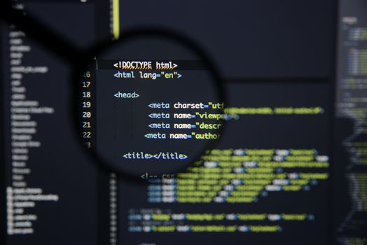 Real Html code developing screen. Programing workflow abstract algorithm concept. Lines of Html code visible under magnifying lens.