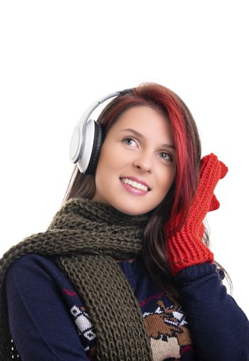 Beautiful smiling young girl with scarf and mittens listening to music on her headphones, isolated on white background.