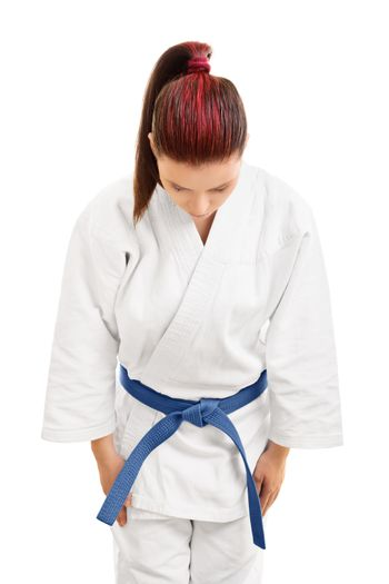 A portrait of a young girl in a white kimono with blue belt bowing, isolated on white background.