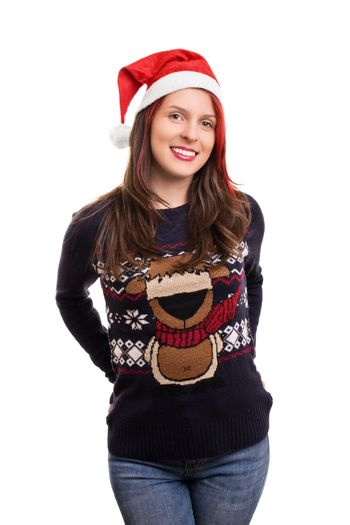 Beautiful young smiling girl wearing a Christmas hat and sweater, isolated on white background.