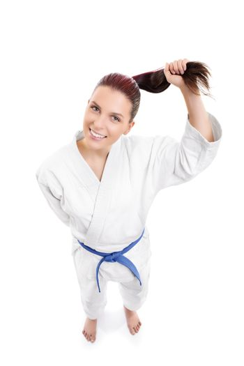 Top down view of a beautiful young smiling girl in a white kimono with blue belt holding her ponytail, isolated on white background.
