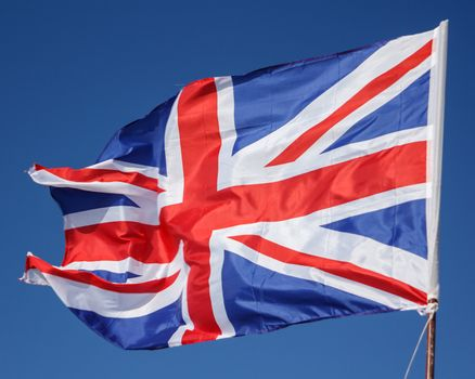 Closeup of Great Britain Flag waving, Flag of the United Kingdom Waving in Wind on Clear Sky. British National Flag. Union Jack. Great Britain Flag Of Silk On Blue Background
