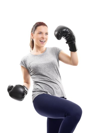 A portrait of a young beautiful girl with boxing gloves cheering and celebrating her success, isolated on white background.
