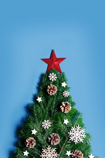 Christmas tree made of natural spruce branches deecor with red star on blue background, flat lay card with copy space