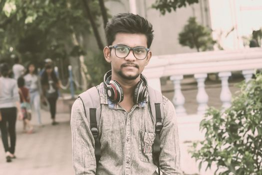 Half length portrait of attractive young a man called Ahok standing outdoors with modern headphones and looking at camera. A music student portrait photography on 21 June, World Music Day.