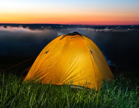 Tent in steppe near river at sunrise