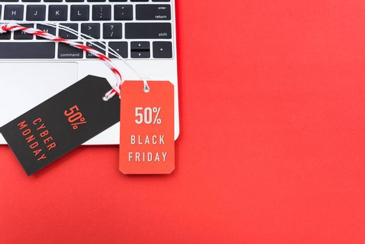 Online shopping Black Friday text with red tag and Cyber Monday text with black tag label on laptop computer, with copy space red background