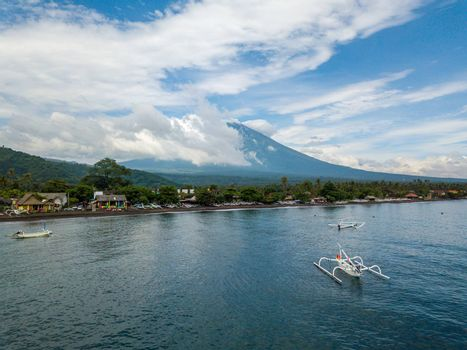 Aerial view of Amed Beach and Mount Agung volcano in Bali, Indonesia. Traditional fishing boats called jukungs in the foreground.