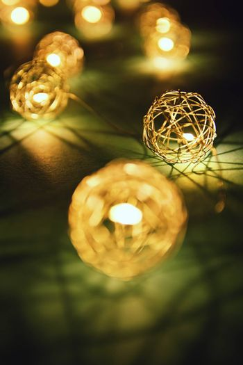 Close up shot of blurred golden Christmas lights making cozy and romantic atmosphere. Festive bukeh background with lights.