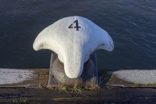 Metal white bollard from Rotterdam harbour with number four - Image