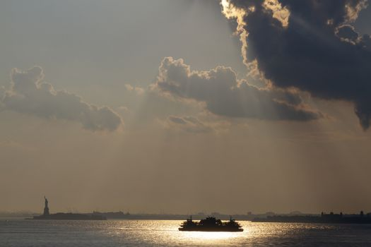 Ferry cruises past the Statue of Liberty on a sunset. Manhattan, New York City, USA