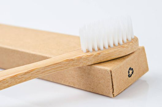 Bamboo toothbrushes on brown paper box with recycle sign on white background.