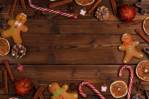Christmas food frame. Gingerbread cookies, spices and decorations on wooden background with copy space