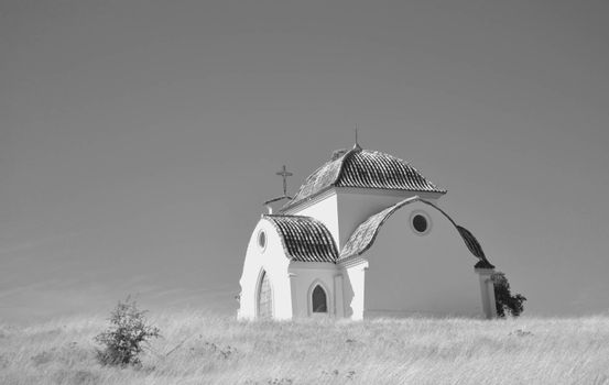 Small hermitage in black and white in the countryside to celebrate pilgrimages in spring