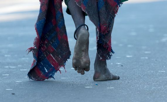 Poverty in Africa - Man wlaking barefoot on a road