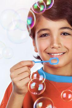 Happy boy blowing bubbles