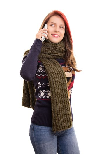 A portrait of a smiling beautiful young girl in winter clothes talking on a phone, isolated on white background.