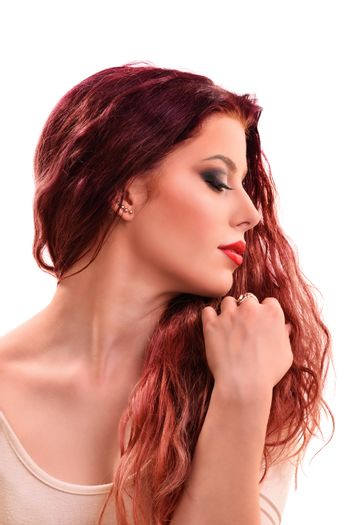 Sensual profile portrait of a beautiful redhead young woman with smoky make up holding her hair, isolated on white background.