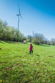 Petite fille qui court dans un champ devant une éolienne