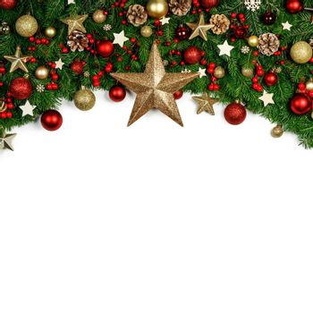 Christmas Border frame of tree branches around white background with copy space isolated, red and golden decor, berries, stars, cones