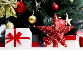 Decorated Christmas gifts and star under tree with baubles isolated on white background